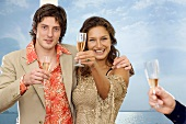 Young couple raising glasses of sparkling wine