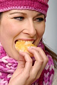 Woman eating a piece of orange