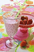 Strawberry shake and strawberries in a glass pedestal bowl