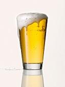 Überschäumendes helles Bier im Glas