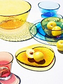Yellow plums and coloured glass tableware