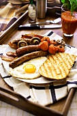 English breakfast: bacon, fried egg, sausages, tomato