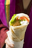 Person holding wrap filled with falafel (chick-pea balls)