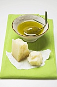 Green olive in small bowl of olive oil, Parmesan