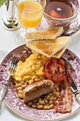 Breakfast with sausage, bacon, beans, scrambled egg, toast & tea (UK)