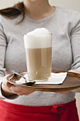 Woman serving caffe latte on tray