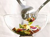 Mixed salad in glass bowl with salad servers