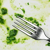 Remains of spinach on plate with fork (close-up)