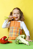 Girl biting into a fresh carrot