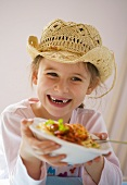 Laughing girl holding plate of spaghetti bolognese