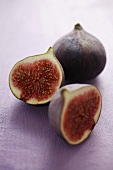 Figs, whole and halved, on mauve background