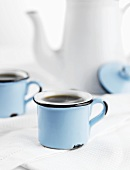 Coffee in blue cups in front of white coffee pot