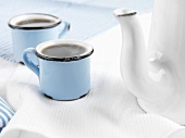 Coffee in blue cups beside white coffee pot