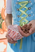 Girl in German national dress holding roasted almonds (Oktoberfest)