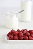 Fresh raspberries, jar of yoghurt in background