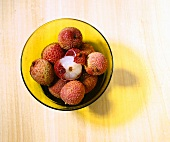 Lychees in yellow glass bowl (overhead view)