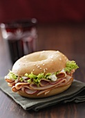 Sesame bagel filled with turkey ham and radishes