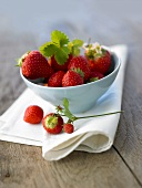 Fresh strawberries in a small bowl on napkin