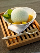 Tea ice cream with orange segments in a white bowl