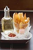 Potato wedges in a glass, salt, ketchup, oil