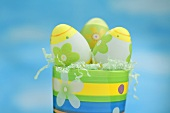Painted Easter eggs in colourful pot