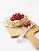 Redcurrant puff pastry tart on chopping board