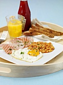 Hearty breakfast with fried egg and baked beans on tray