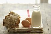 Bottle of milk, eggs and bread on tea towel