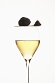 Black truffle and spoonful of caviar on glass of champagne