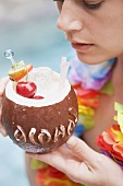 Woman holding coconut drink with fresh fruit