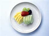 Apple and pineapple slices, grapes and strawberry on plate