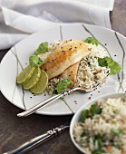 Fish fillet with slices of lime on basmati rice