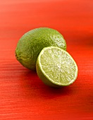 Whole and half lime on red background