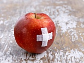 A red apple with a sticking plaster cross