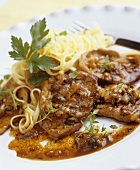 Veal escalopes with onions and ribbon pasta