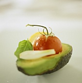 Avocado half with tomato, onion and basil