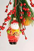 Weihnachtsmann als Baumschmuck und Ilexbeeren am Kiefernzweig