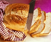 A loaf of white bread with knife