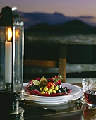 Plate of olives on laid table by the sea (by candlelight)