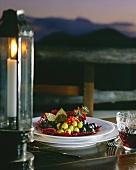 Teller mit Oliven auf gedecktem Tisch am Meer bei Kerzenlicht
