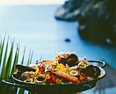 Paella in a pan, cliffs and sea in the background