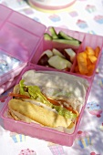 Club sandwich with vegetables in pink lunch box