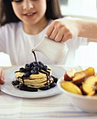Girl pouring chocolate sauce over pancakes and blueberries