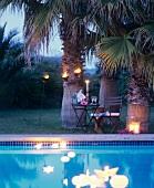 Sekt bei Kerzenschein unter Palmen am Pool