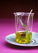 Olive oil with black olive and olive sprig