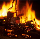 Cognac in glasses and bottle in front of open fire