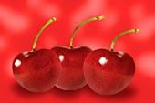 Three cherries against red background