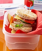 Salami cheeseburger in wholemeal toast in plastic storage box