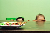 Two boys peeping at sweets over the edge of a table