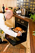 Man dressed for dinner party putting a duck into the oven
